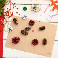 Making Christmas decorations: directly above view of wax crayons, handmade toy, Christmas wreath and colorful fir cones lying on wooden desk